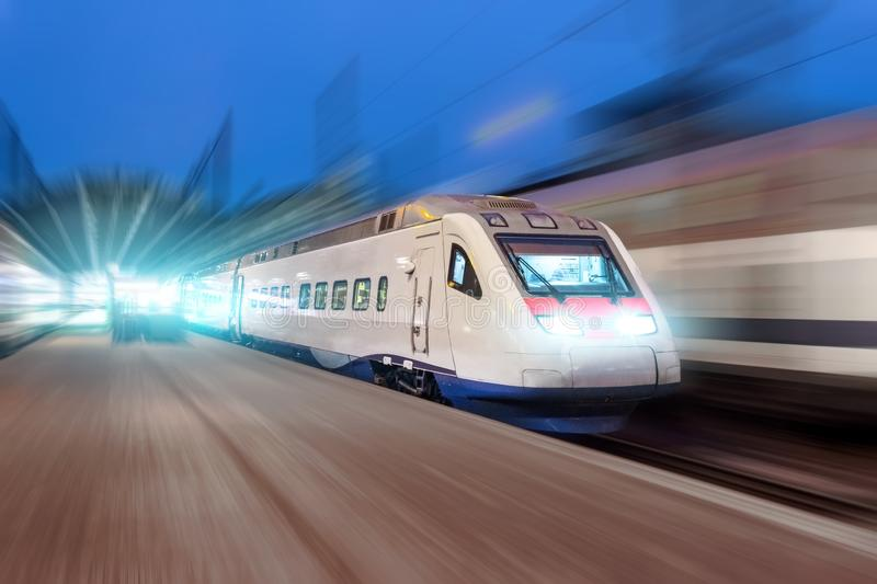 Night railway station, a passing train at speed.  stock photography