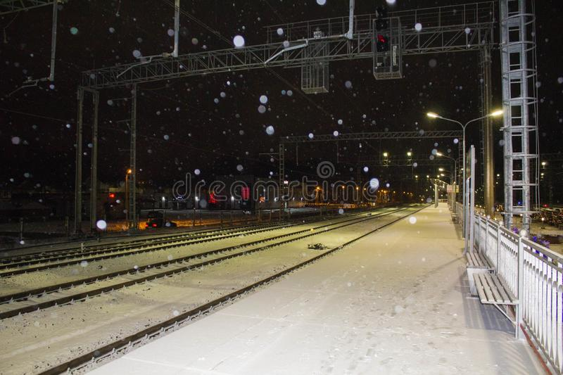 Night railway station. Snowfall. The lights of the city in the background. stock photos