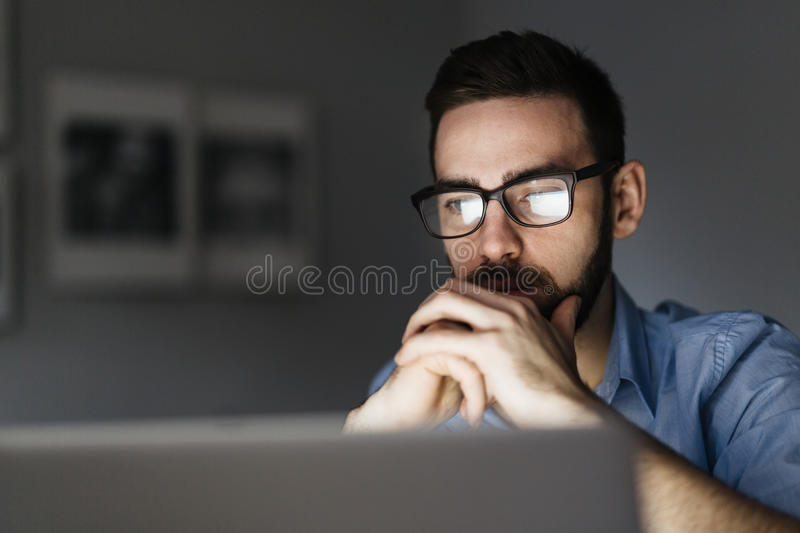 Night reading. Pensive analyst reading information in the net royalty free stock image