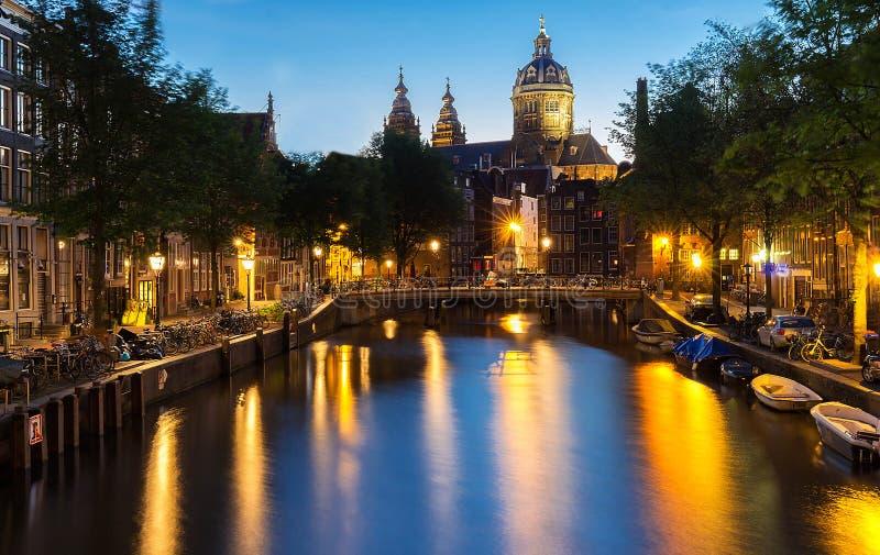 Night red-light district De Wallen, canal, Basilica of Saint Nicholas and bridge, Amsterdam, Holland. Long exposure. stock photo