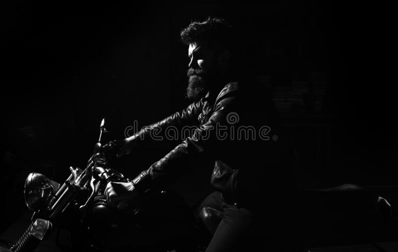 Night rider concept. Hipster, brutal biker in leather jacket riding motorcycle at night time, copy space. Man with beard. Biker in leather jacket sitting on royalty free stock photo