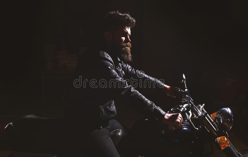 Night rider concept. Hipster, brutal biker in leather jacket riding motorcycle at night time, copy space. Man with beard. Biker in leather jacket sitting on stock images