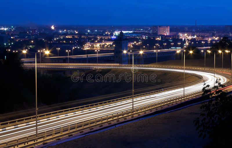 Night road. Sunset. Night road. A small amount of cars. A city on a background stock images