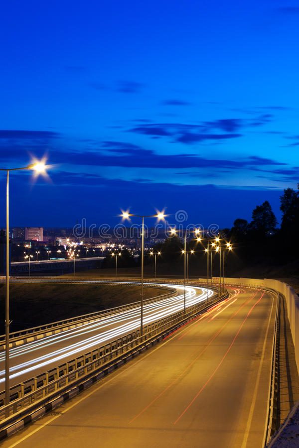 Night road. Sunset. Night road. A small amount of cars. A city on a background royalty free stock photos