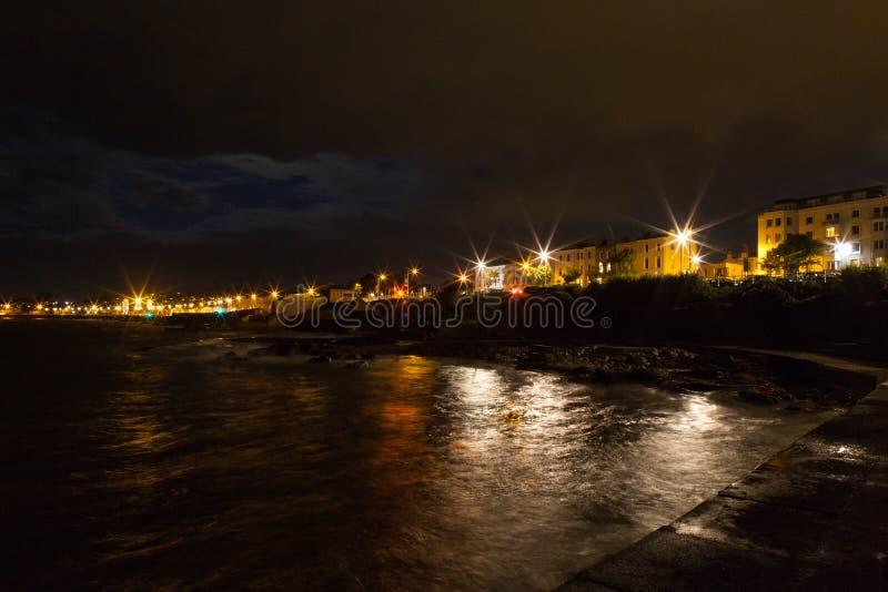 Night rocky sea coast and city lights royalty free stock photo