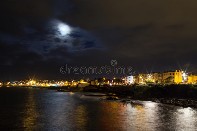Night rocky sea coast and city lights royalty free stock images