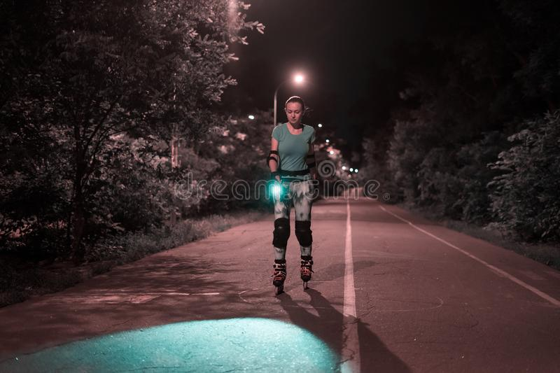 Night roller skating of eoung sports girl on a road royalty free stock photos