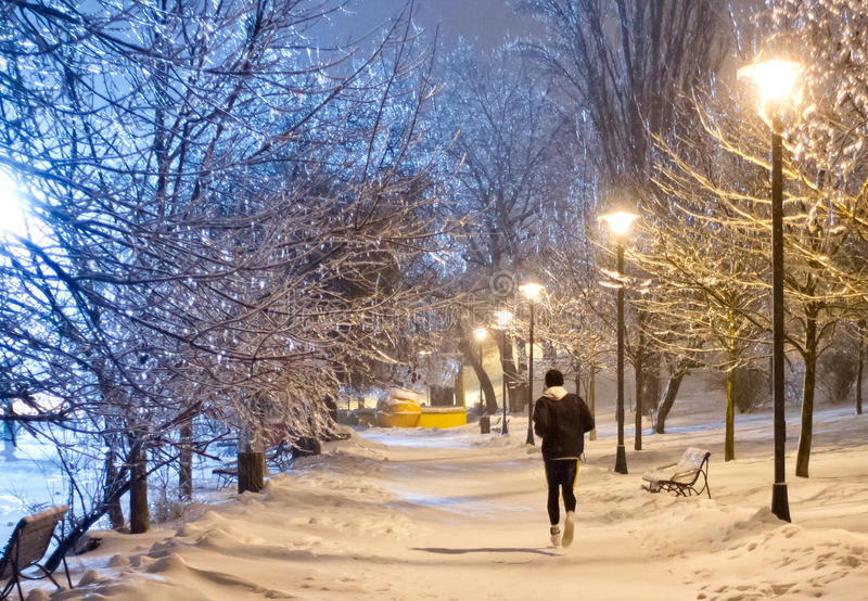Night running in the snowy park royalty free stock images