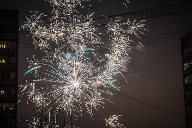 Night salute. Explosion lines of different colors. Outbreaks between houses. Night salute. Explosion lines of different colors. between housesnNight salute royalty free stock photos