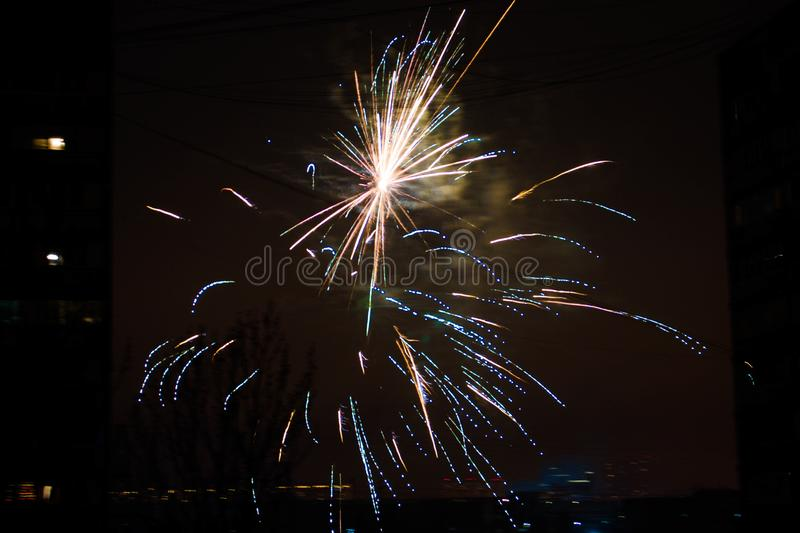Night salute. Explosion lines of different colors. Outbreaks between houses. Night salute. Explosion lines of different colors. between housesnNight salute royalty free stock photo