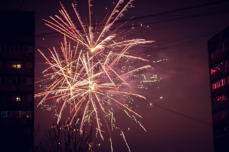 Night salute. Explosion lines of different colors. Outbreaks between houses. Night salute. Explosion lines of different colors. between houses stock photography