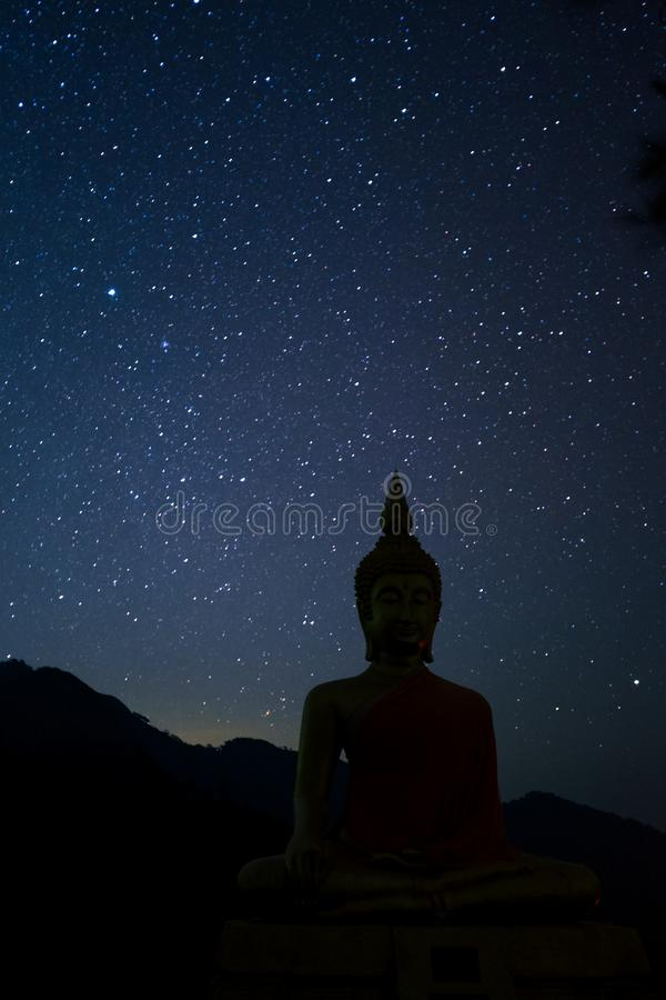 Night scape with beautiful stary sky and buddha image stand at the high mountain. Space background. I. Night scape with beautiful stary sky and buddha image stock image