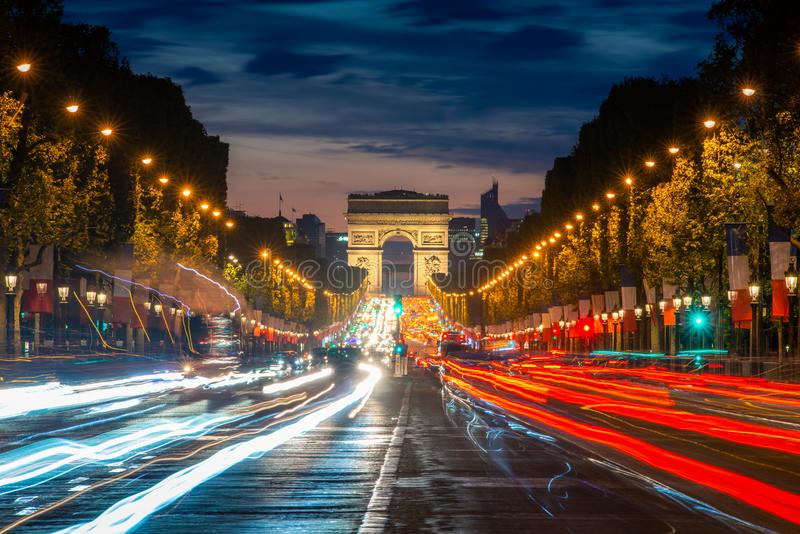 Night scence illuminations traffic street of the Impressive Arc de Triomphe Paris along the famous tree lined Avenue des Champs-. Elysees in Paris, France royalty free stock photo