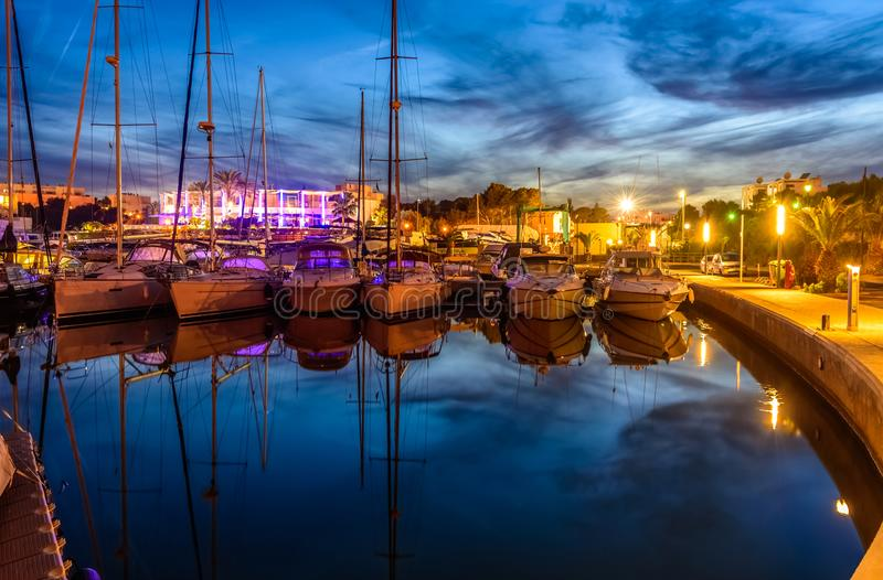 Night scene of Cala Dor port in Mallorca. Amazing and romantic night scene in Cala Dor port, with lights reflected in water. Palma de Mallorca, Spain royalty free stock photos