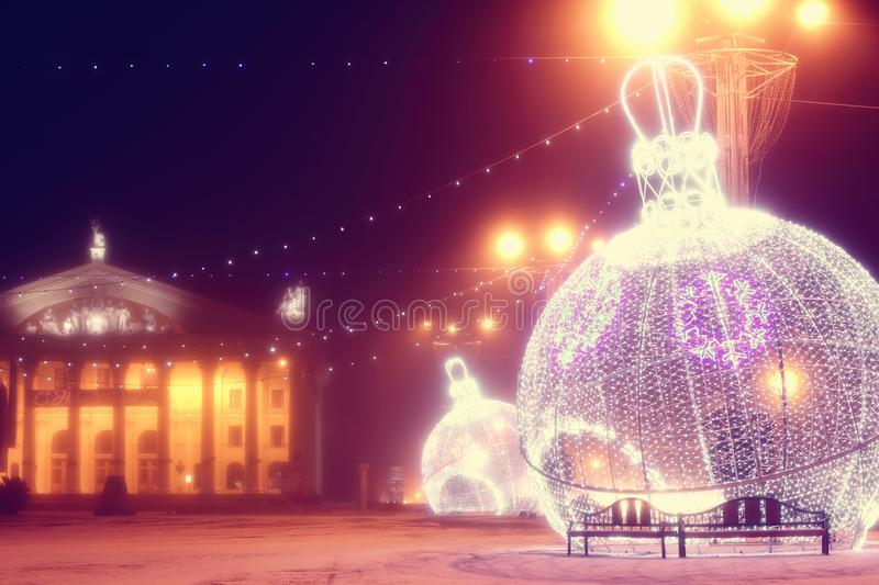 Night scene with illuminated Christmas balls and theater. Beautiful night scene with illuminated Christmas balls in the early morning fog. Picture taken on the stock photography