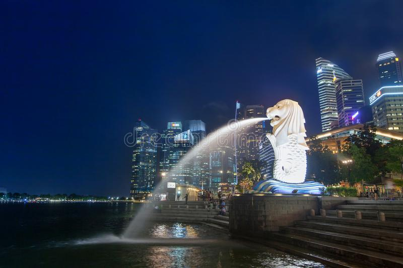 Night scene of illuminated Merlion fountain in Singapore. Night scene of illuminated Merlion fountain and modern business buildings on background stock images