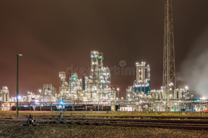 Night scene with illuminated petrochemical production plant and train tracks, Antwerp, Belgium. Night scene with illuminated petrochemical production plant with stock photos
