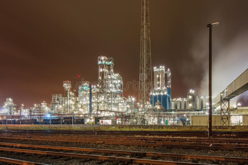Night scene with illuminated petrochemical production plant and train tracks, Antwerp, Belgium. Night scene with illuminated petrochemical production plant and royalty free stock photos