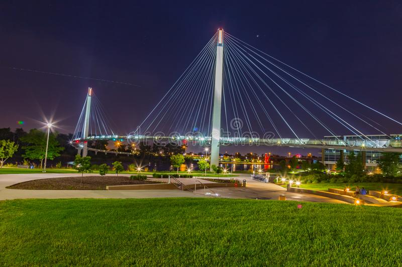 Night scene of Omaha Nebraska Bob Kerrey suspension bridge. Towers with suspension cables with beautiful sky colors just after sunset. Omaha Nebraska skyline stock photo