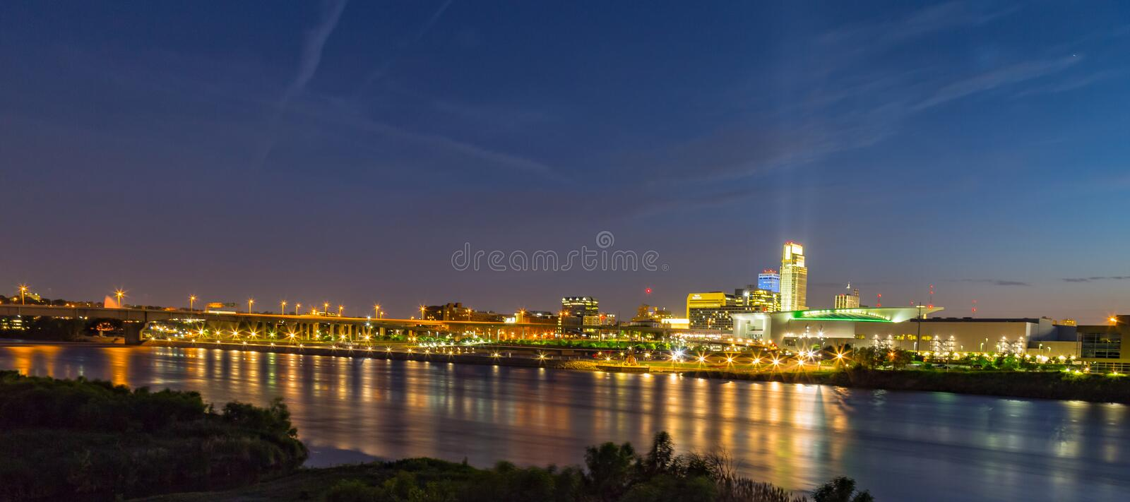 Night scene of Omaha waterfront with light reflections on the r Omaha Nebraska skyline with beautiful sky colors just after sunset royalty free stock image
