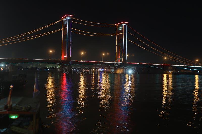Night scene in Palembang, Sumatera, Indonesia. Night scene of the Ampera Bridge in Palembang, Sumatera, Indonesia the river and the boat at the pier stock photos