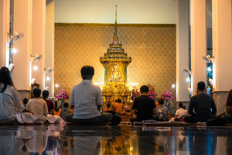 Night scene of people meditating in the temple. Wat Pathum Wanaram temple. royalty free stock photography