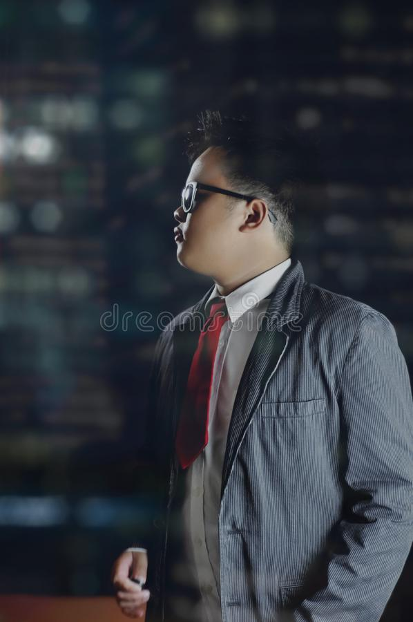A night scene portrait of a business man looking at something on his left side inside an office. royalty free stock photography