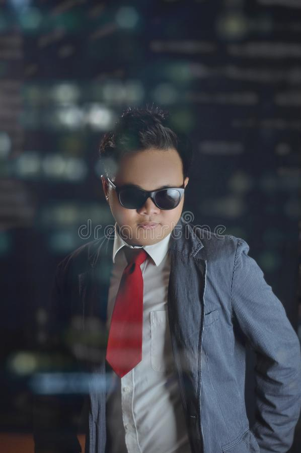 Young male in suit and red tie and eyeglasses looking serious directly to the camera. stock photo