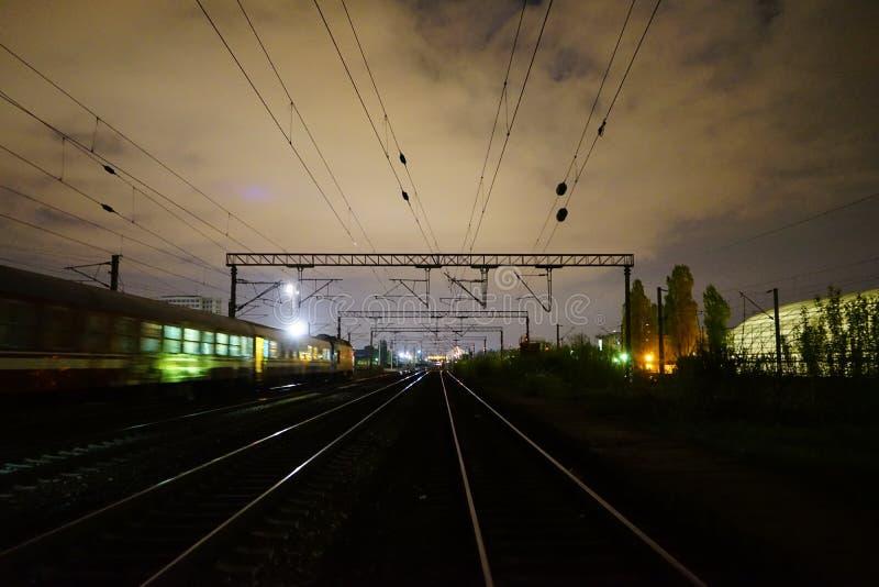 Night scene of rails and train in Carpati station, Bucharest, CFR. Train passing Carpati station in Bucharest Romania nightscene stock image