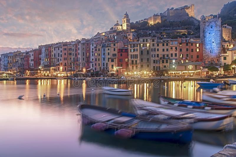 Night scene with reflections in Portovenere. Night scene with waterfront reflections and blurred fishing boats in the tranquil harbour of Portovenere, Liguria royalty free stock photography