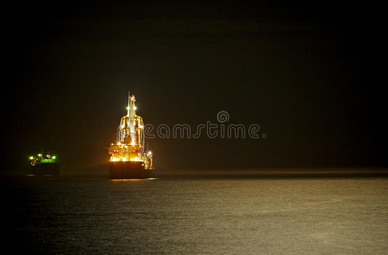 Night scene of a sea horizon with lunar path and illuminated ships royalty free stock images