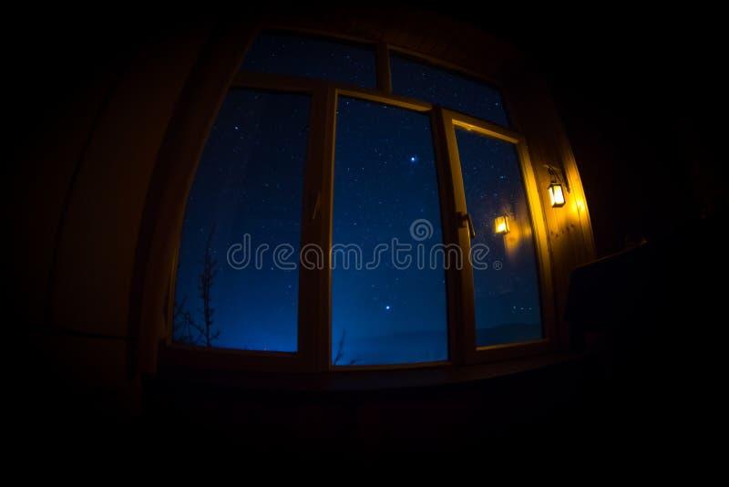 Night scene of stars seen through the window from dark room. Night sky inside dark room. Long exposure shot. Night scene of stars seen through the window from stock images