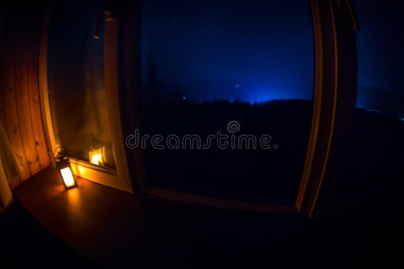 Night scene of stars seen through the window from dark room. Night sky inside dark room. Long exposure shot. Night scene of stars seen through the window from stock photo