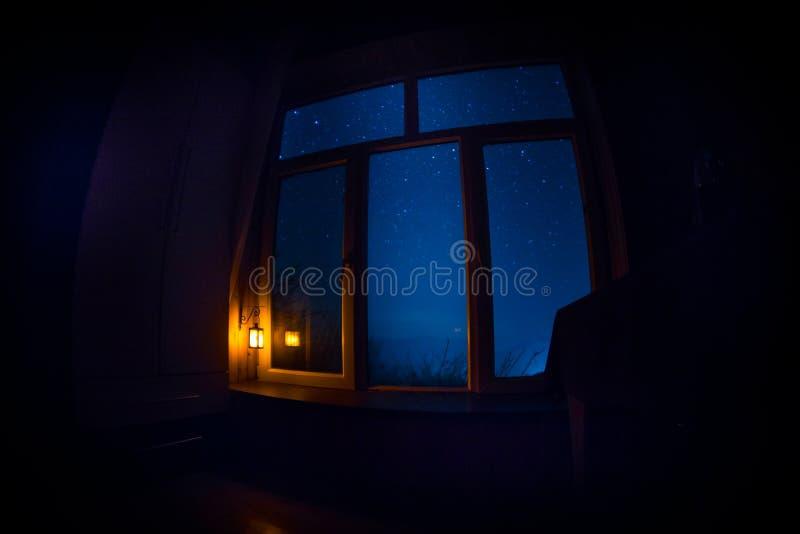 Night scene of stars seen through the window from dark room. Night sky inside dark room. Long exposure shot. Night scene of stars seen through the window from stock photography