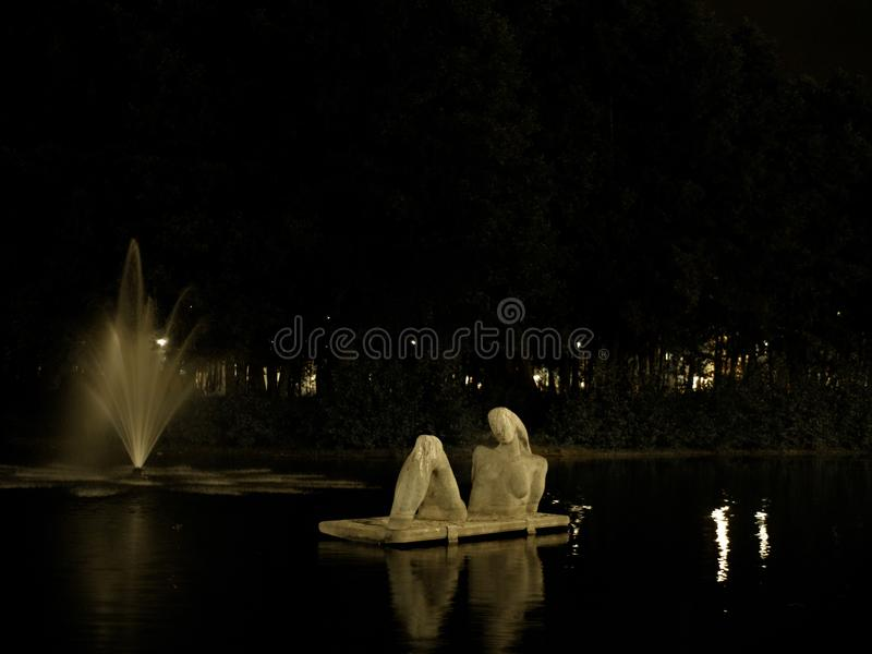 A night scene, statue and a water fountain stock photography