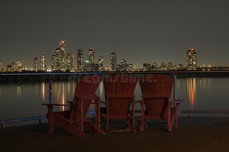 Night scene of wooden chairs at the waterfront lookout with a view of night lights of a cityscape. Night scene of wooden chairs at the waterfront lookout with a stock photos