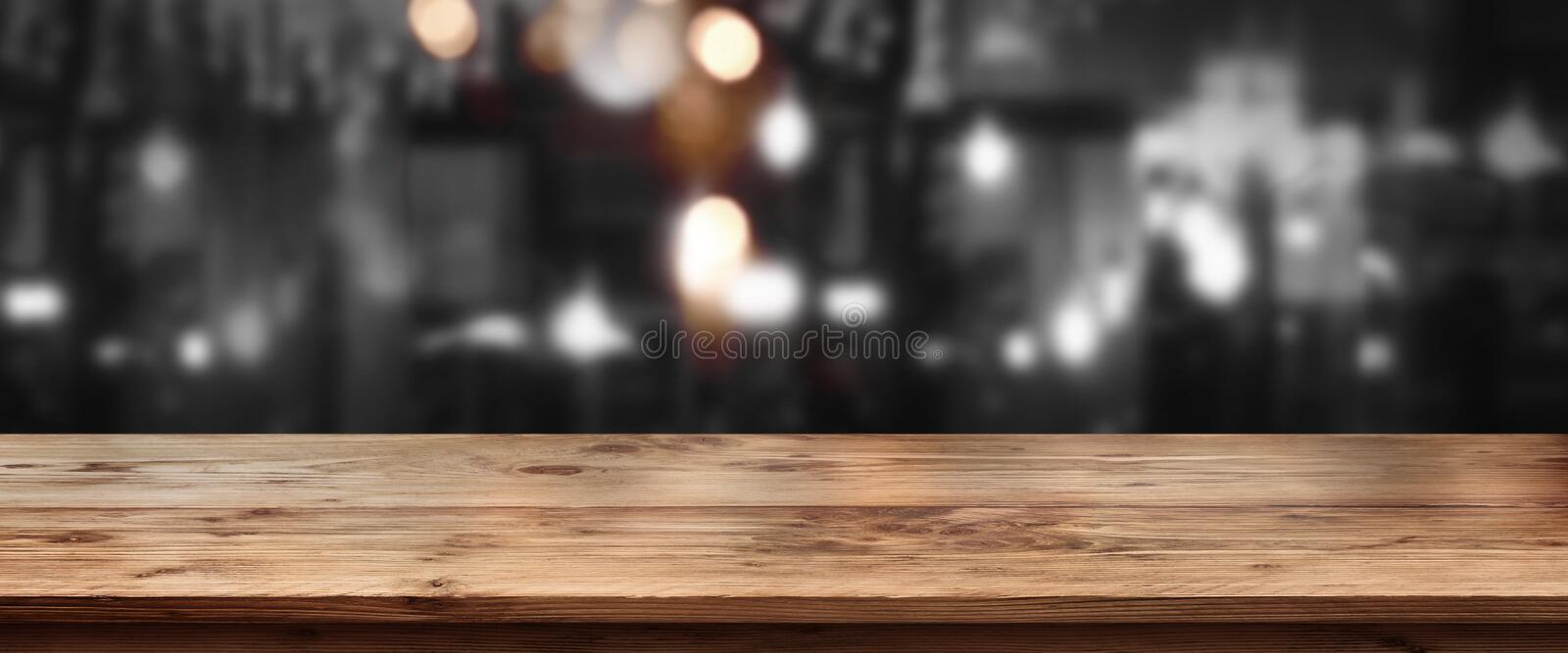 Night scenery at a bar. Scenery at night in a bar with bright lights in front of an empty wooden table stock image