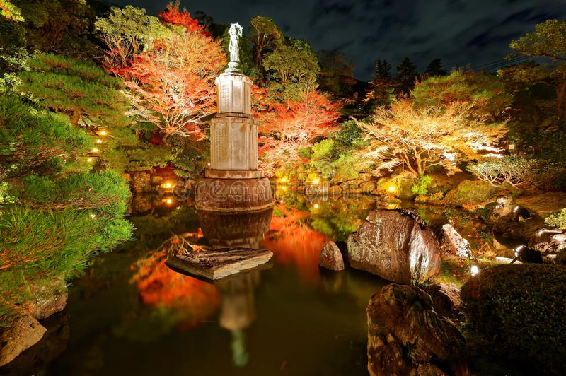 Night scenery of a beautiful Japanese Garden in Chion-In Buddhist temple in Kyoto. Japan, with a statue of Goddess of Mercy in the pond and illuminated maples royalty free stock photo