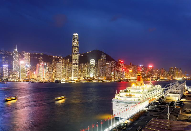 Night scenery of Hong Kong with a skyline of crowded skyscrapers by Victoria Harbor, a luxury cruise liner parking by the pier  royalty free stock photo