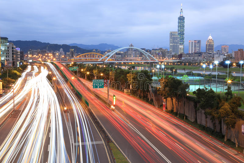 Night scenery of Taipei City, with Taipai 101 in Xin-Yi District, downtown area with arch bridges and car trails on Avenue stock photography
