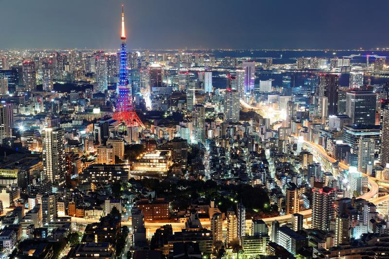 Night scenery of Tokyo, with an aerial panoramic view of illuminated Tokyo Tower among crowded buildings in downtown area stock photo