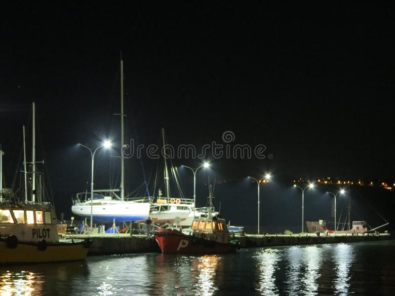 Night scenery view of yachts in night harbor with light reflections on the water. Sea port waterfront evening panorama. Night scenery view of yachts in night stock photo