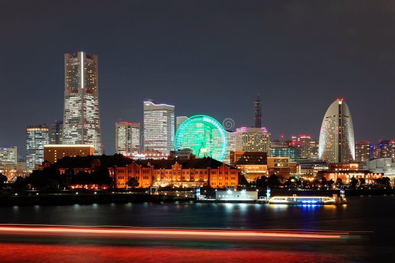 Night scenery of Yokohama Minatomirai Bay Area with Landmark Tower among modern skyscrapers. In background, a giant Ferris wheel in an amusement park & colorful stock image