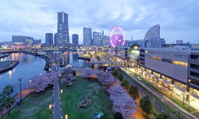 Night scenery of Yokohama Minatomirai Bay Area, with view of high rise skyscrapers in the background. A giant Ferris wheel in Cosmo Amusement Park & beautiful stock image