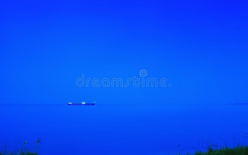 Night Seascape With Cargo Ship On The Horizon royalty free stock image