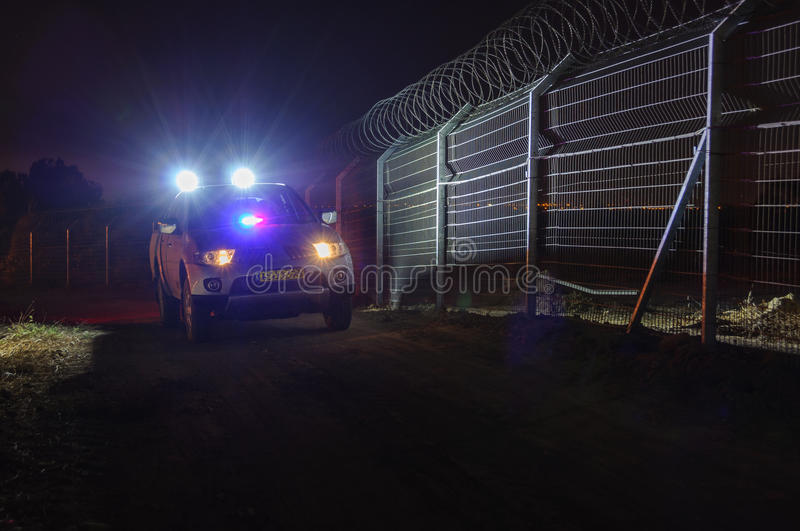 Night, security patrol car moving along the fence. Security patrol car moving at night on the trail along the peripheral defense fence in a remote rural area stock photo