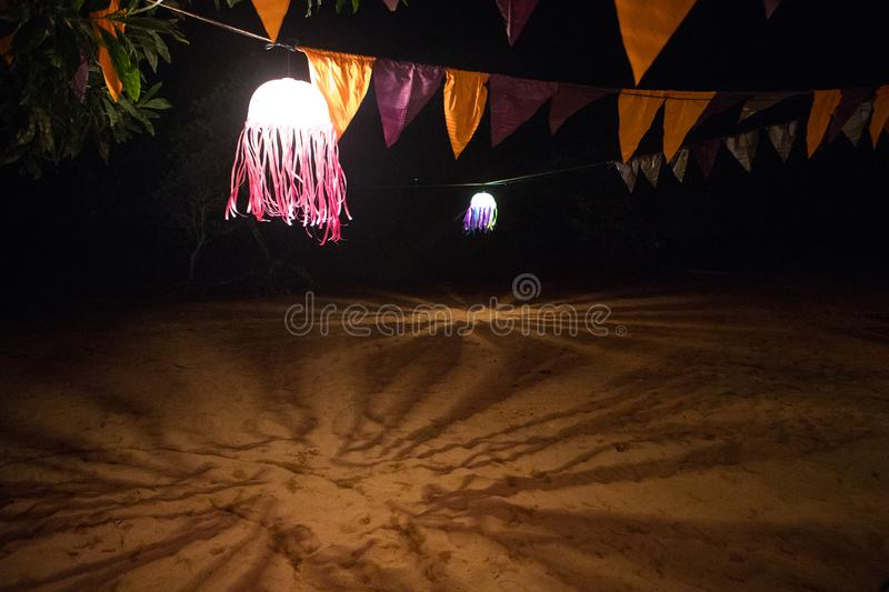 Night shadows from a traditional Asian lantern on the sand stock image