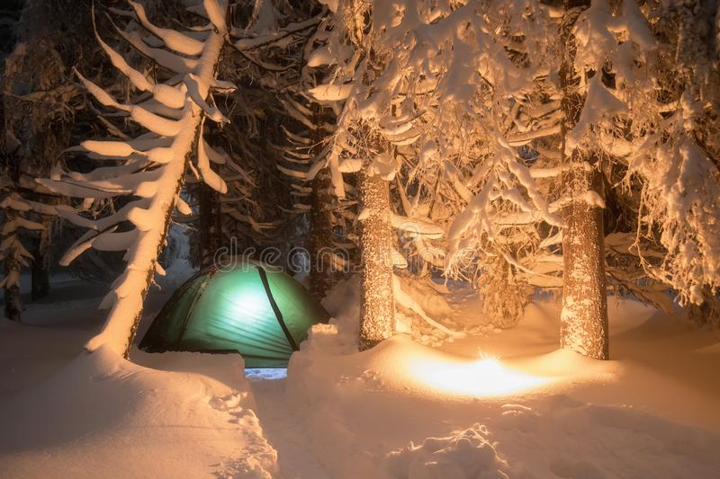 Night shot of burning fire, long exposure, sleeping in the snow outside. Night bivouac in the mountains. Christmas time. Night shot of burning fire, long royalty free stock images