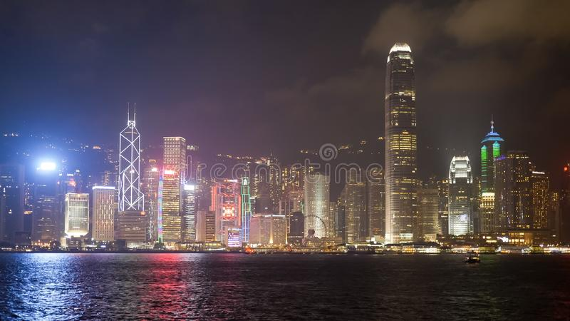 Night shot of the IFC building and victoria harbour in hong kong. A night view of victoria harbour and the IFC building from tsim sha tsui promenade in hong kong stock images