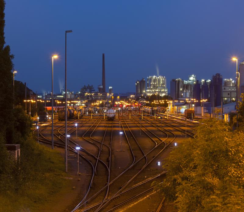 Industry Railroad Yard At Night. Night shot of an industrial railroad yard with several trains, a refinery in the background stock photography